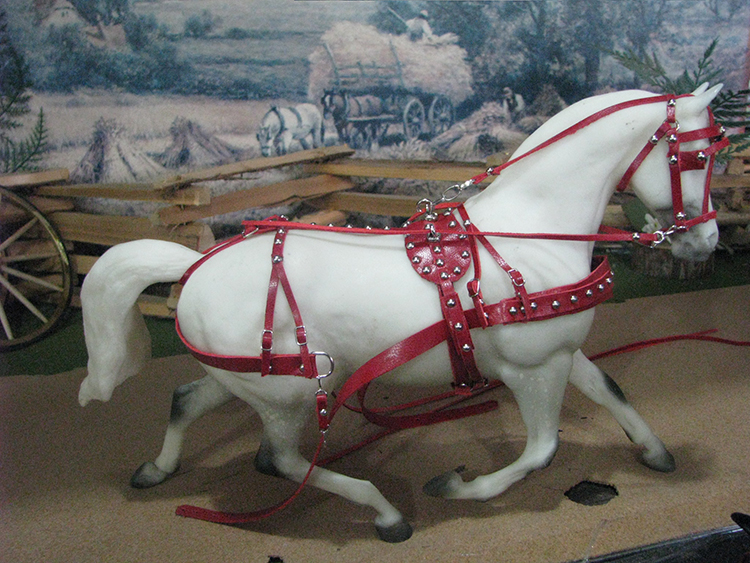 red driving harness on white horse